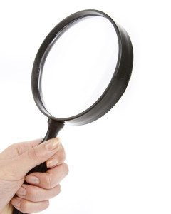 Hand holding magnifying glass. Plain background