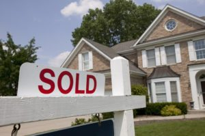 Sold sign in front of single-family house