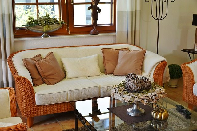 orange wicker couch next to coffee table