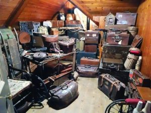 Dozens of suitcases, duffle bags, and boxes packed into a tiny attic.