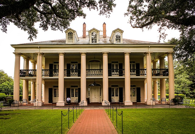 A two-story Greek Revival plantation home with tall columns, wrap-around porches, and a grassy lawn.