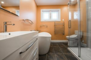 A large bathroom with white countertops, a white standing tub, white bidet, frameless glass shower, and orange walls.