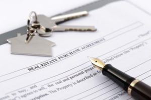 """Pad of paperwork with the title """"Home Purchase Agreement"""" with a pen and set of keys."""
