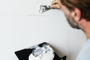 Man applying plaster to a wall in his home.