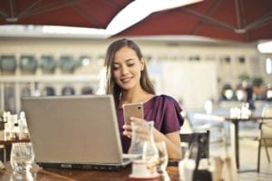 Woman in a purple shirt sitting outside at a coffee shop table with her cell phone in one hand looking at a laptop screen.