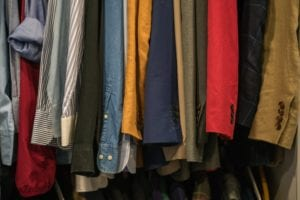 A row of clothes hanging in a closet.
