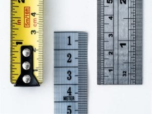 Measuring tape and two rulers laying on a white surface.