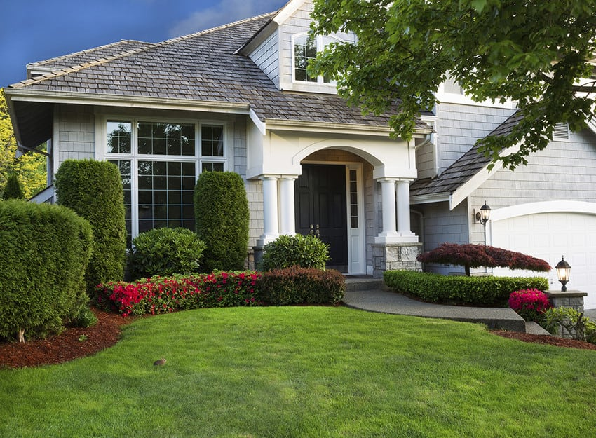 The front exterior of a home that's been manicured with trimmed shrubs and flower beds.