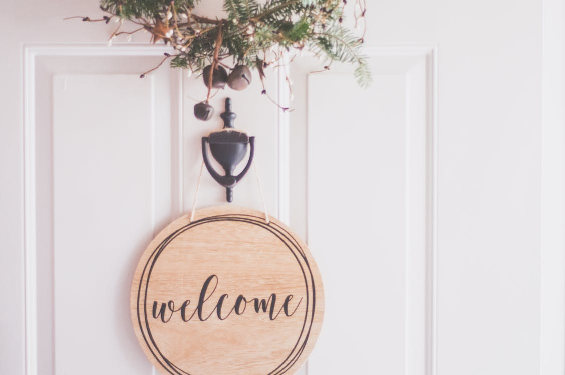 A welcome sign and a small wreath on a white front door.