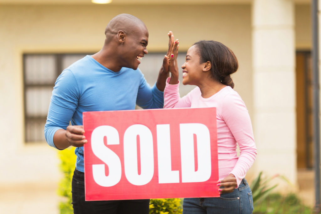 couple with a sold sign