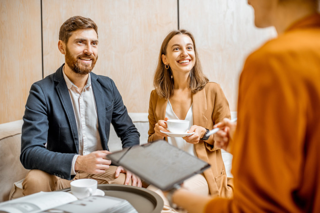 couple meeting with realtor over coffee